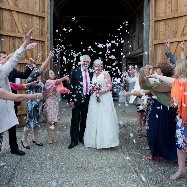 Wedding couple with confetti in Sullington tithe barn, West Sussex